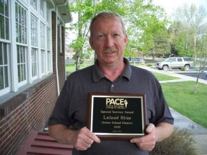 Former Director of Operations, Leland Bliss holds the 2016 PACE Award honoring the Sisters School District