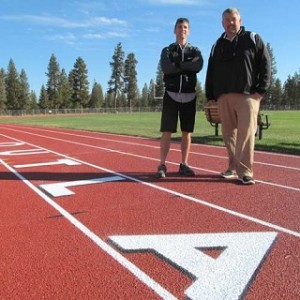 Sisters High School boys and girls track Coach Jeff Larson, left, and project manager Brett Hudson inspect the running track's new surface. photo by Steve Kadel